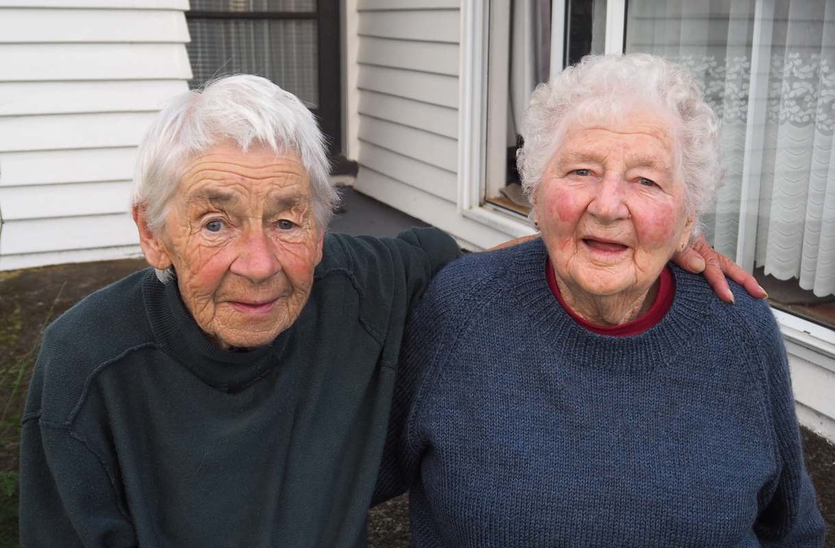 Benna and  Gertie, arms around each other, dressed in blue jerseys, outside their Inglewood home.