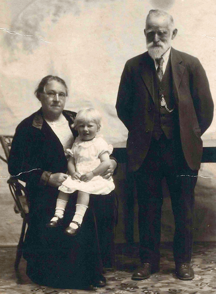 Black and white studio photograph of Benna sitting on Mary Potroz's lap, and with Thomas standing next to them, hands  behind his back.