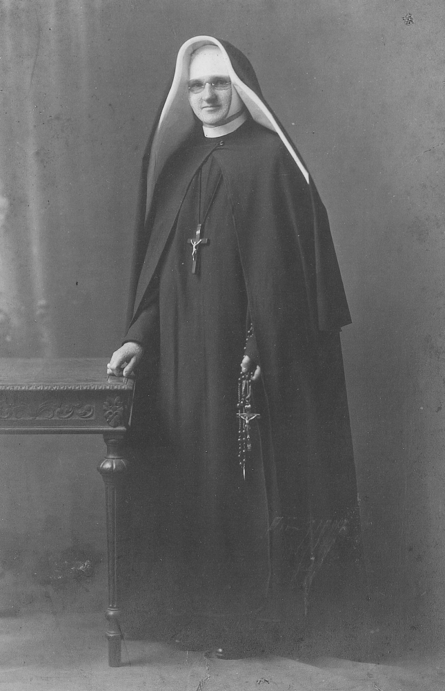Black  and white photograph of Sr Dunstan in her habit, standing next to a carved table and holding a large-beaded rosary with a  crucifix nearly as big as her hand.