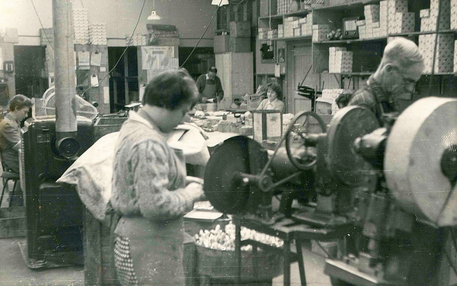 Black and white photograph  the factory floor. In the foreground is a machine and immediately behind are a young woman and older man working separately.  In the background are three other people, heads down, at desks, and shelves filled with boxes.