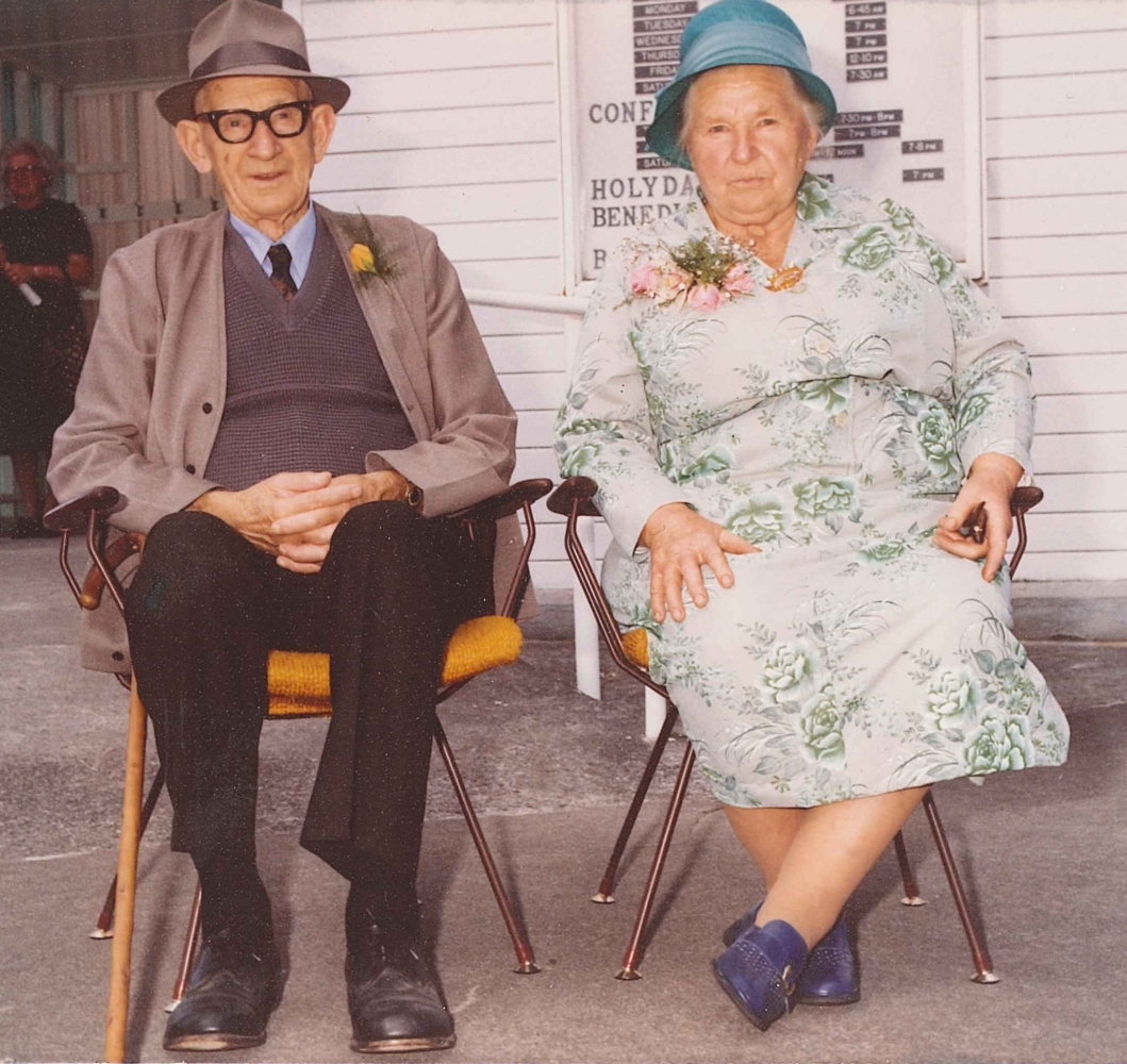 Coloured informal photograph of Jacob and Ellen sitting on chairs with mustard-coloured seats, outside the church.  Ellen is in a white, long-sleeved dress with green roses and is wearing a turquoise-coloured hat. She looks serious. Jacob,  in a light-brown hat that matches his jacket and waistcoat, smiles.
