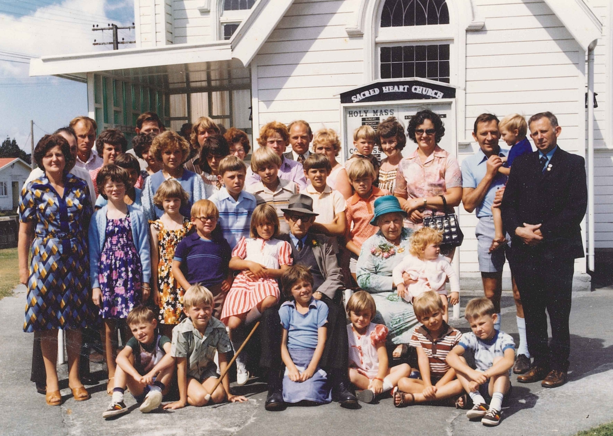Coloured informal group photograph of Jacob and Ellen surrounded by their large family. Both Jacob and Ellen have  children on their laps. This time, Ellen smiling. A lovely sunny day.