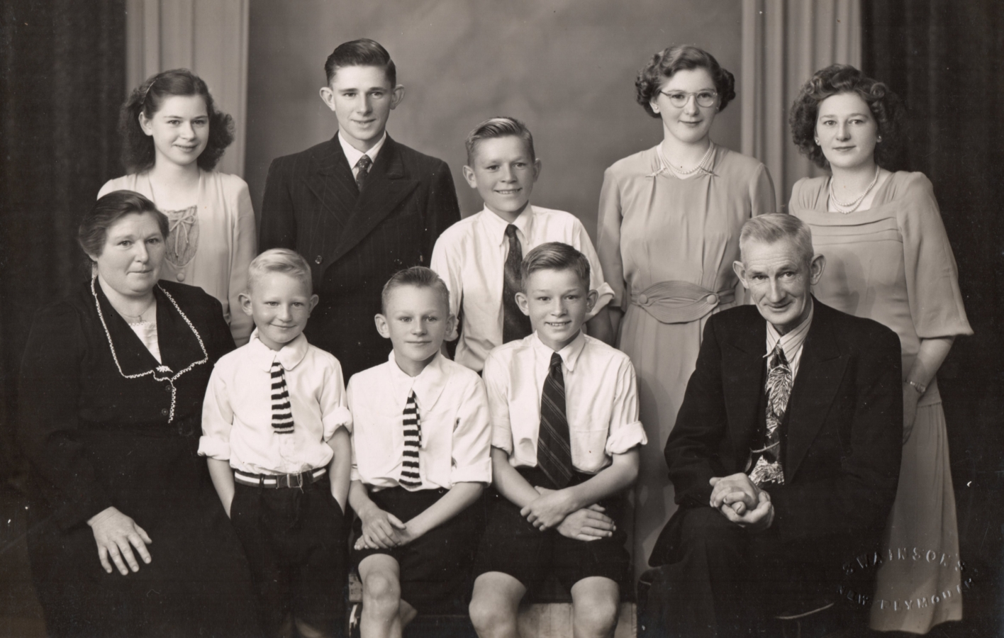 Black and white studio photograph of the family: Jacob and Joseph in suits and ties, and the four younger boys in white shirts and ties,  Ellen in a formal dress suit, and the girls in dresses. All are smiling sweetly.