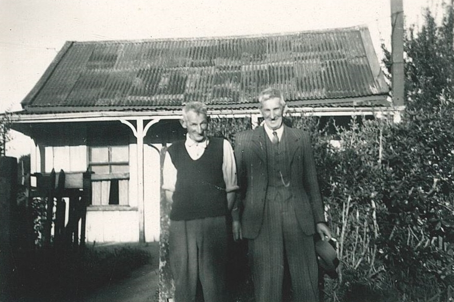 Black and  white photograph of Jacob and Frank standing outside the old house, Frank in a three-piece suit and holding his hat, and  Jacob more casual in rolled-up shirt-sleeves and a knitted sleeveless jumper. The dodgy curve in the corrogated iron roof is  clearly visible.