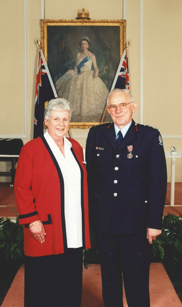 Coloured  formal photograph of Joe and Patsy Kuklinski in front of a formal portrait of a young Queen Elizabeth II flanked by two New  Zealand flags. Joe is in his formal fire service uniform, with the QSM. Patsy is in a long black skirt, white shirt and red  jersey-jacket etched in black.
