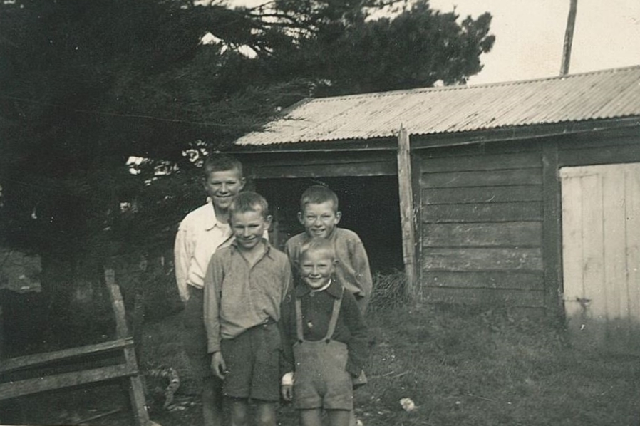 Black and white  photograph of the four boys, aged about five to , standing close together in front of a rough-hewn single-storey barn, all  smiling widely, two at the back, two at the front. The one behind the smallest boy is bending slightly and has an  extra-impish grin.