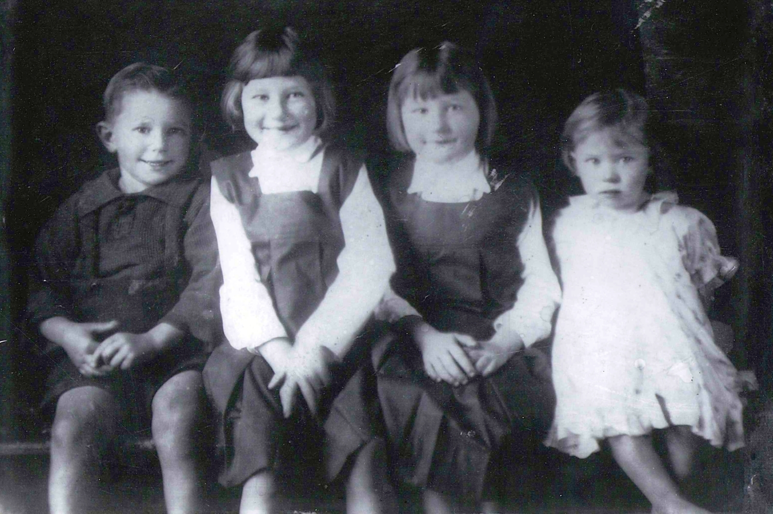 Black and white photograph of the first four Kuklinski children, sitting: Benna and Pauline in the middle with too-large gym-lips, and with  similar page-boy hair cuts, Joseph on one side in shorts and a dark shirt smiling as widely as Benna, and Gertie on the other  side in a frilly dress looking slightly more suspiciously at the photographer.