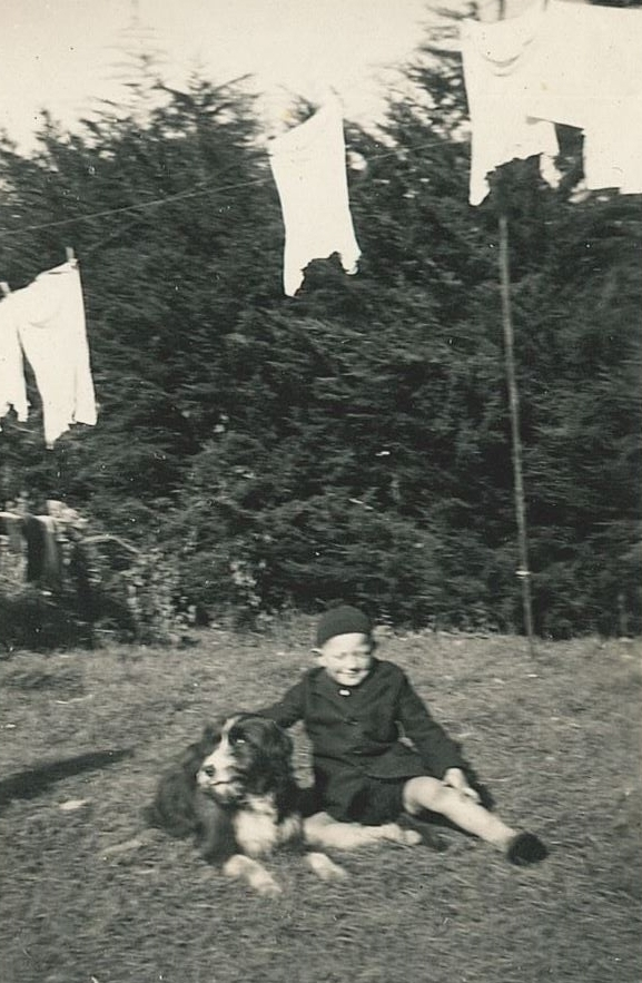 Slightly blurry  black and white photograph of a boy aged about seven, in school uniform, sitting on the grass with a huge hairy dog, in front  a high hedge. Some washing, unclear what but white, is still on the line.