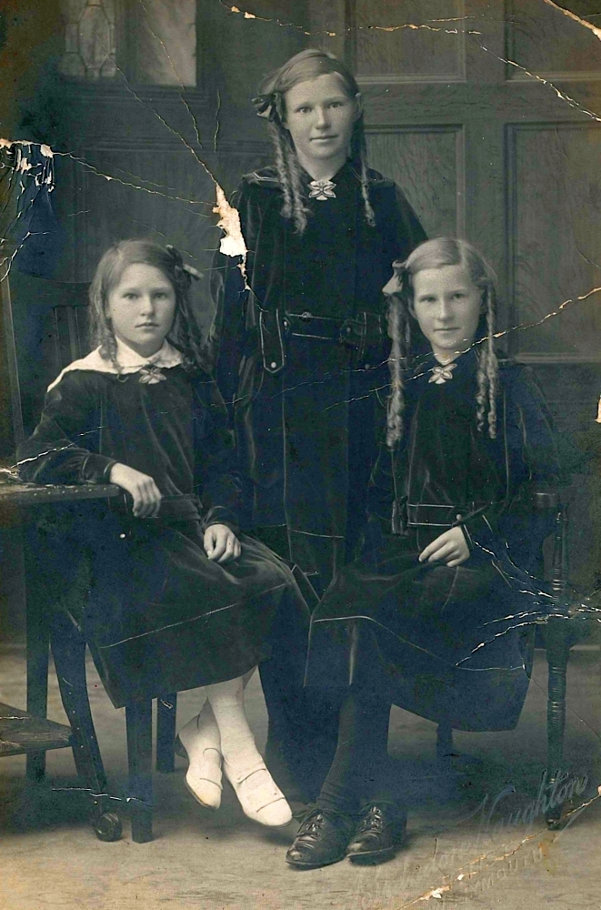 Black and white  studio photograph of the youngest Potroz siblings in dark, possibly velvet, dresses. The three bonde girls all have their  long, fair hair curled into locks, each with a ribbon in her hair. Ellen and Millie are half-smiling, but the youngest, Pat,  with her legs crossed at the ankles and not touching the floor, looking more serious.