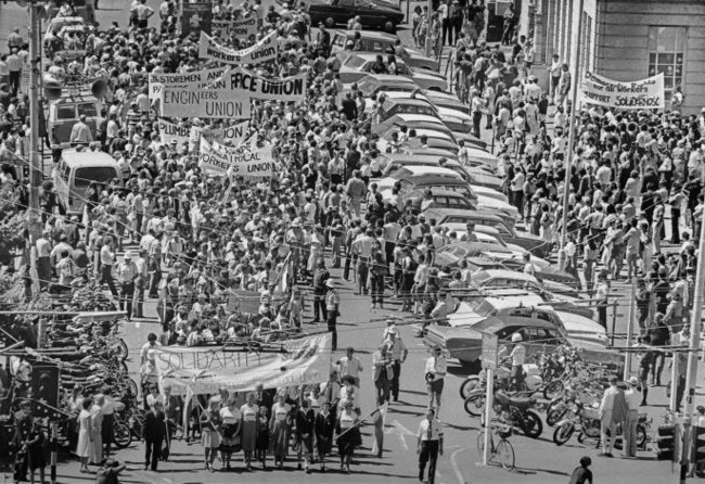 Hundreds of people with trade union banners in a Wellington street