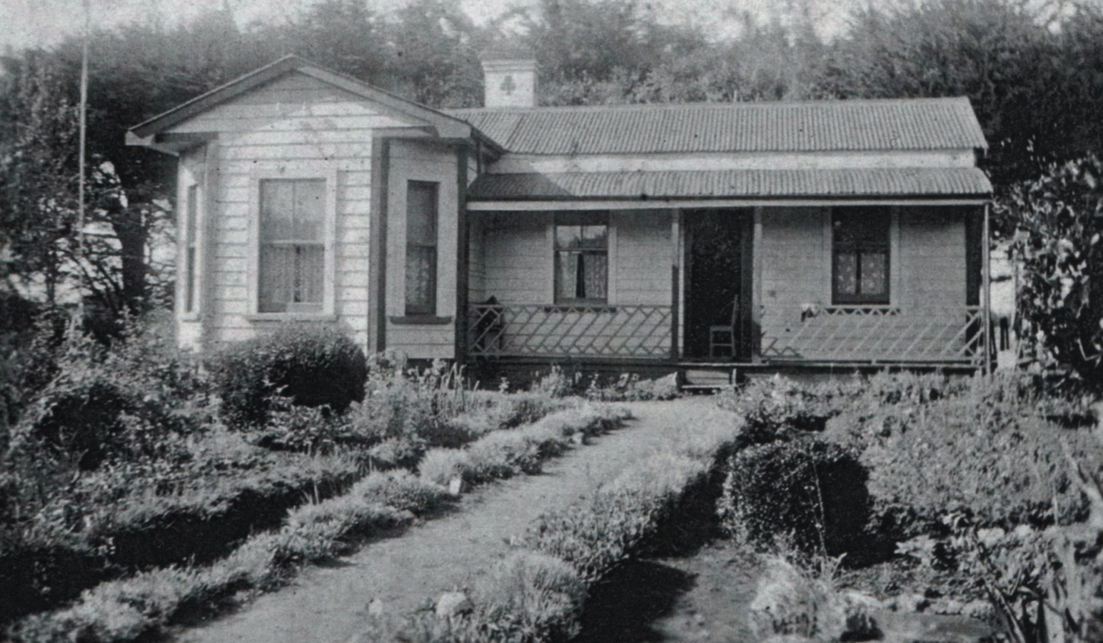 A black and  white photograph of a bungalow with a neat garden on both sides of a straight path in front.