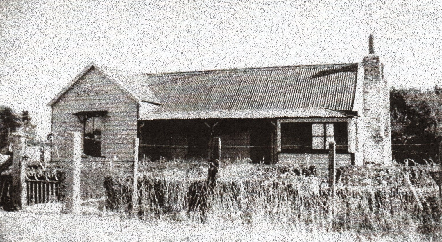 A  black and white photograph of the simple bungalow with corrugated iron roof.