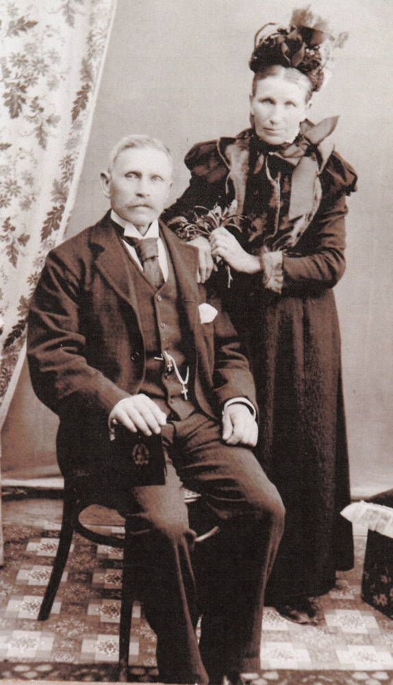A formal studio photograph of Michael Francis and Cecelia, Michael sitting, his hand on a picture of Our Lady, Cecelia  standing behind, hand her husband's shoulder and holding a posie of flowers in the other.