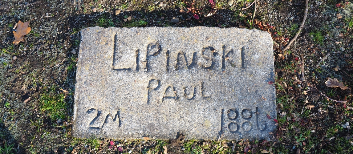 A small concrete  rectangle in the grass, with Paul Lipinski's name hand-written