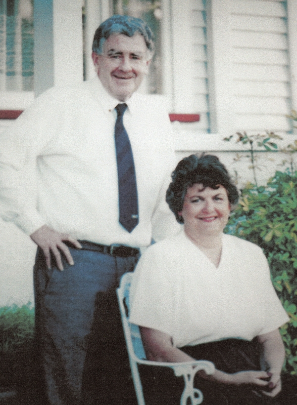 A casual photograph of Ronald, standing, in shirtsleeves, and Roselyn, sitting