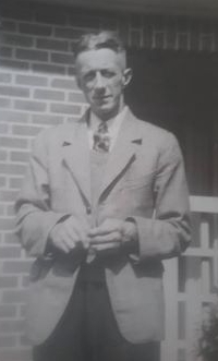 A blurred shot of Alfred in  a light jacket, dark trousers and tie taken outside a house.