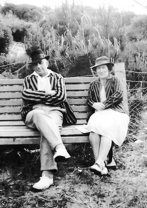 Bert and Edith  sitting on a bench in front of a fenced hill, both in striped jackets, Bert with arms folded