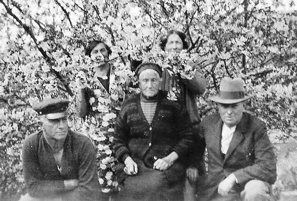 Franciska Orlowski  seated in front of a flowering tree with Bert on one side, another man on the other and two women hidden in the blossoms.