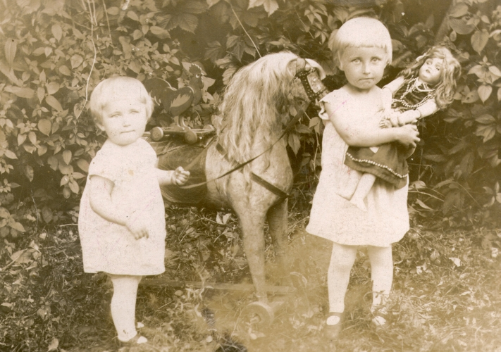 Janina and  Romka Marchewa, aged about two and four, with doll and wheeled horse in garden
