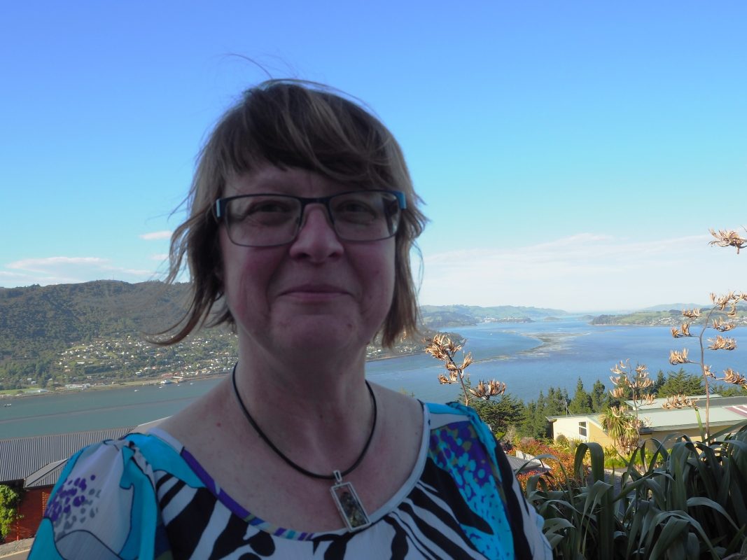 Bożena  Misiewicz-Haug on a balcony at her home, with the Otago peninsula in the background