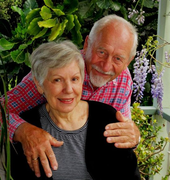 A coloured casual  photograph of Michał behind Zenona and with his arms around her shoulders. Both have warm smiles. Taken in their garden, the  background is a wisteria and other creepers.