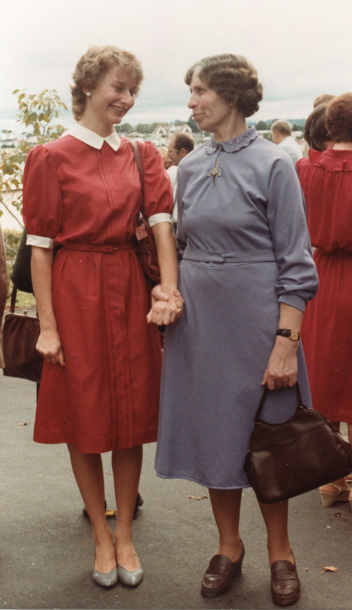 A coloured  photograph of Ciocia Julia and Regina standing, holding hands and looking at each other and smiling, both wearing similar,  high-collared dresses. Ciocia Julia's dress is a duck-grey, and she has a handbag and sensible shoes, and Regina's dress is  red with white trimmings. Her shoes are silver.