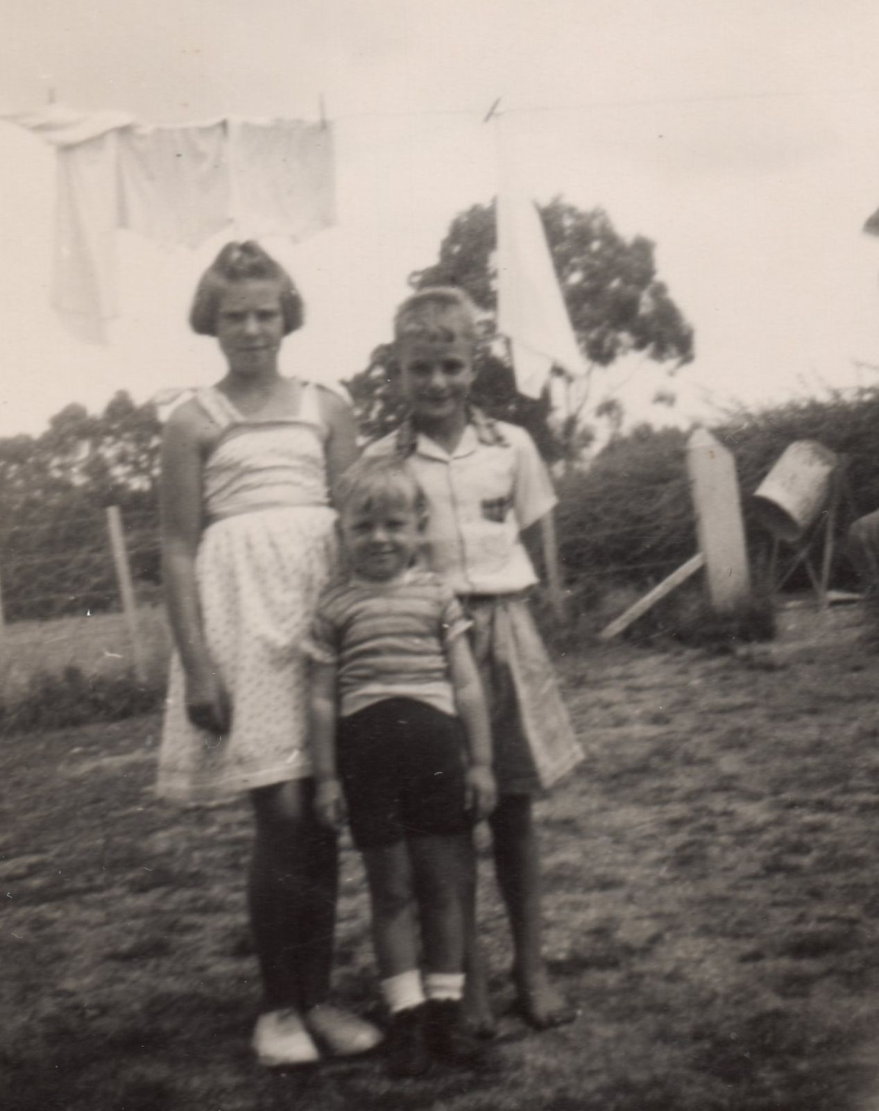 Black  and white pic of the siblings in the garden, Zenona frowning and in a white sundress, her brothers smiling. Immediately  behind them is a washline with white laundry.