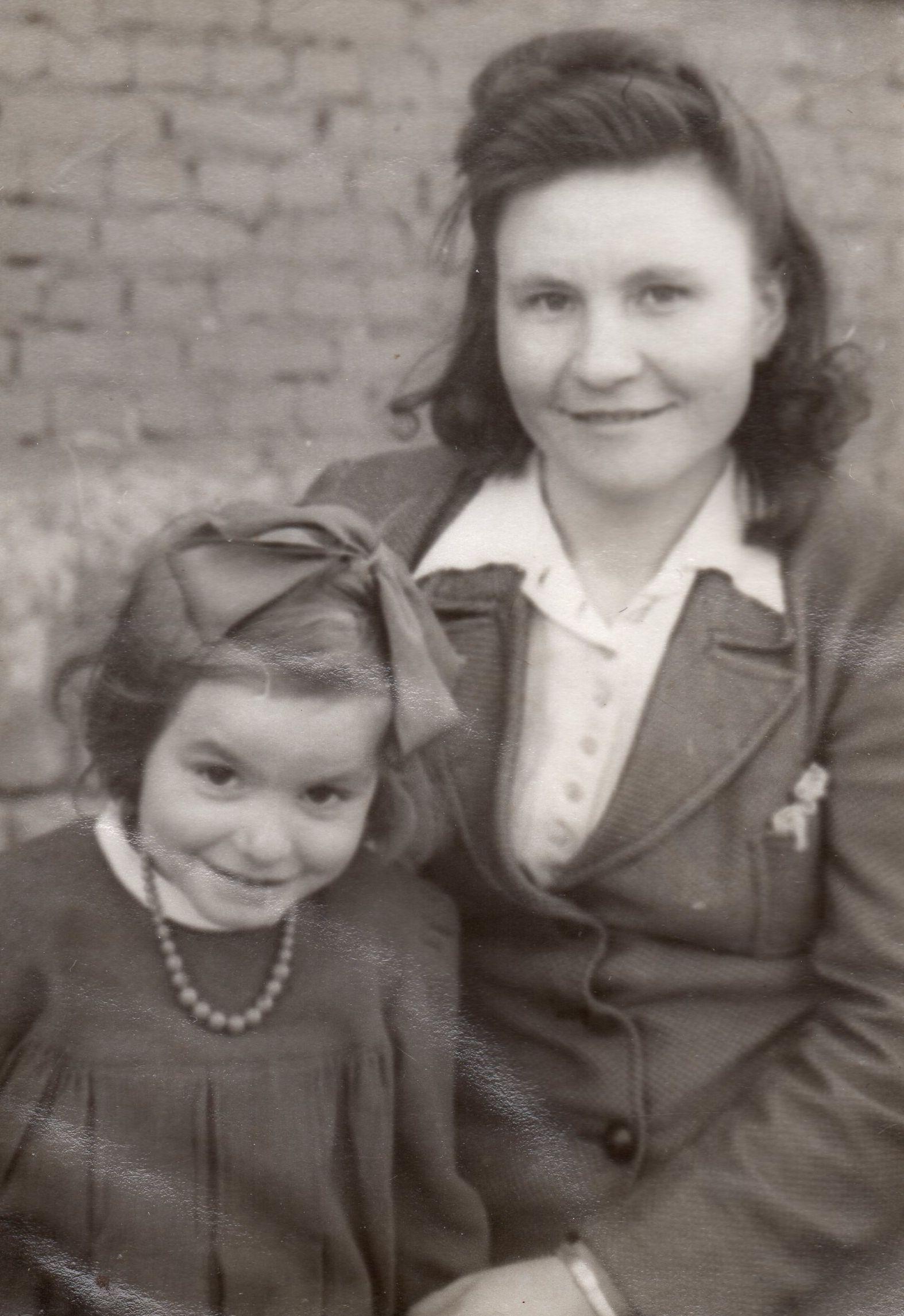 Black  and white pic taken outdoors. Emilija is seated and wearing a jacket and white shirt and Zenona is wearing a dress pleated on  a high bodice, with a necklace and a ribbon in her hair. Both are smiling.