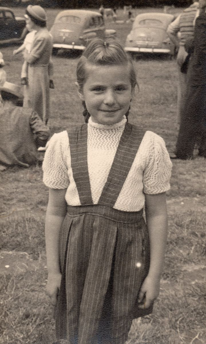 Black  and white pic of Zenona in a paddock, smiling and wearing a dark skirt and pale short-sleeved crocheted top. In the  background are parked cars, circa 1950s, and several members of the public doing their own thing.