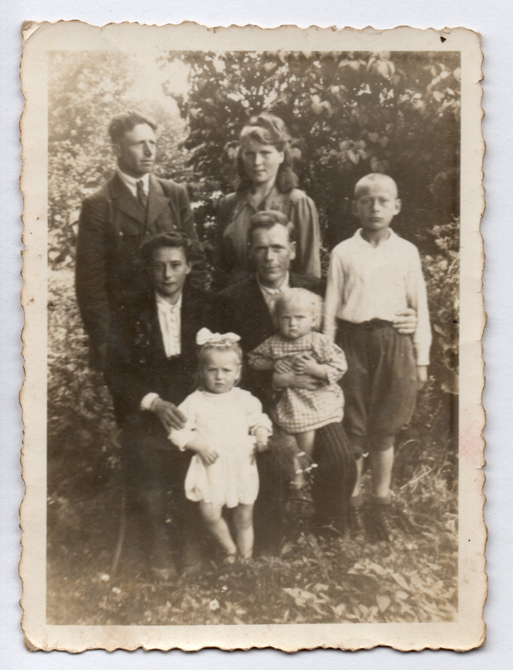A  black and white photo of the family around two adults on chairs. All serious. Uncle Józef's hand around Michał's waist is  clearly seen as he sits with a toddler on his lap next to Michał