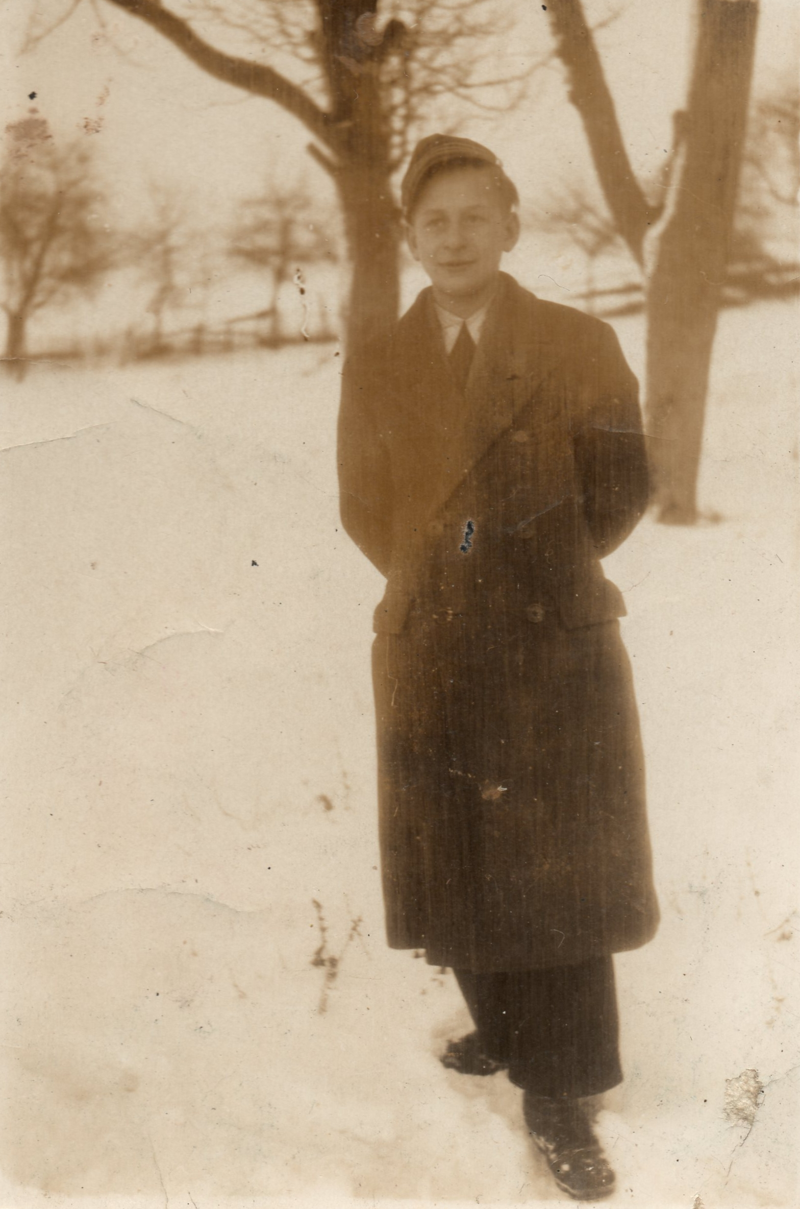 A sepia photograph  of Michal in a winter coat, standing in a field of snow. Trees in the background.