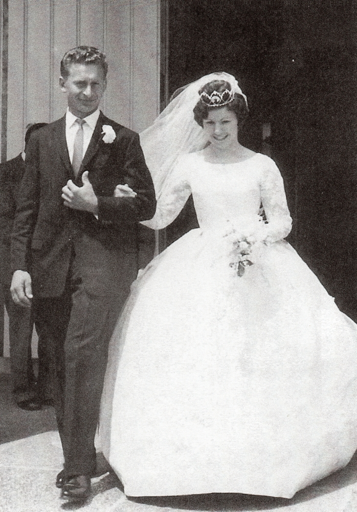 Black  and white pic of Zenona and Michał walking out of the church. Wind is pushing Zenona's short veil. Her dress is long-sleeved  and with a full skirt Wide smiles.