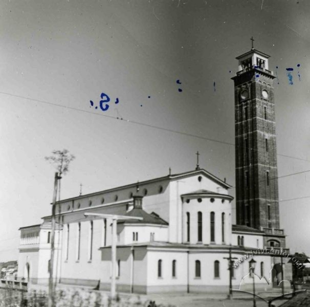 Black and  white picture of the church, white, with the high tower next to it in a darker brick