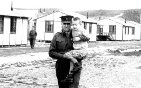 A New Zealand  soldier walks across an empty yard while holding Victor.