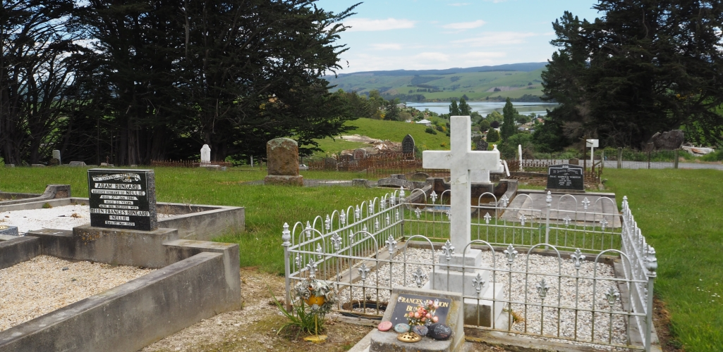 View of some of the headstones at the Waihola cemetery, looking towards the lake.