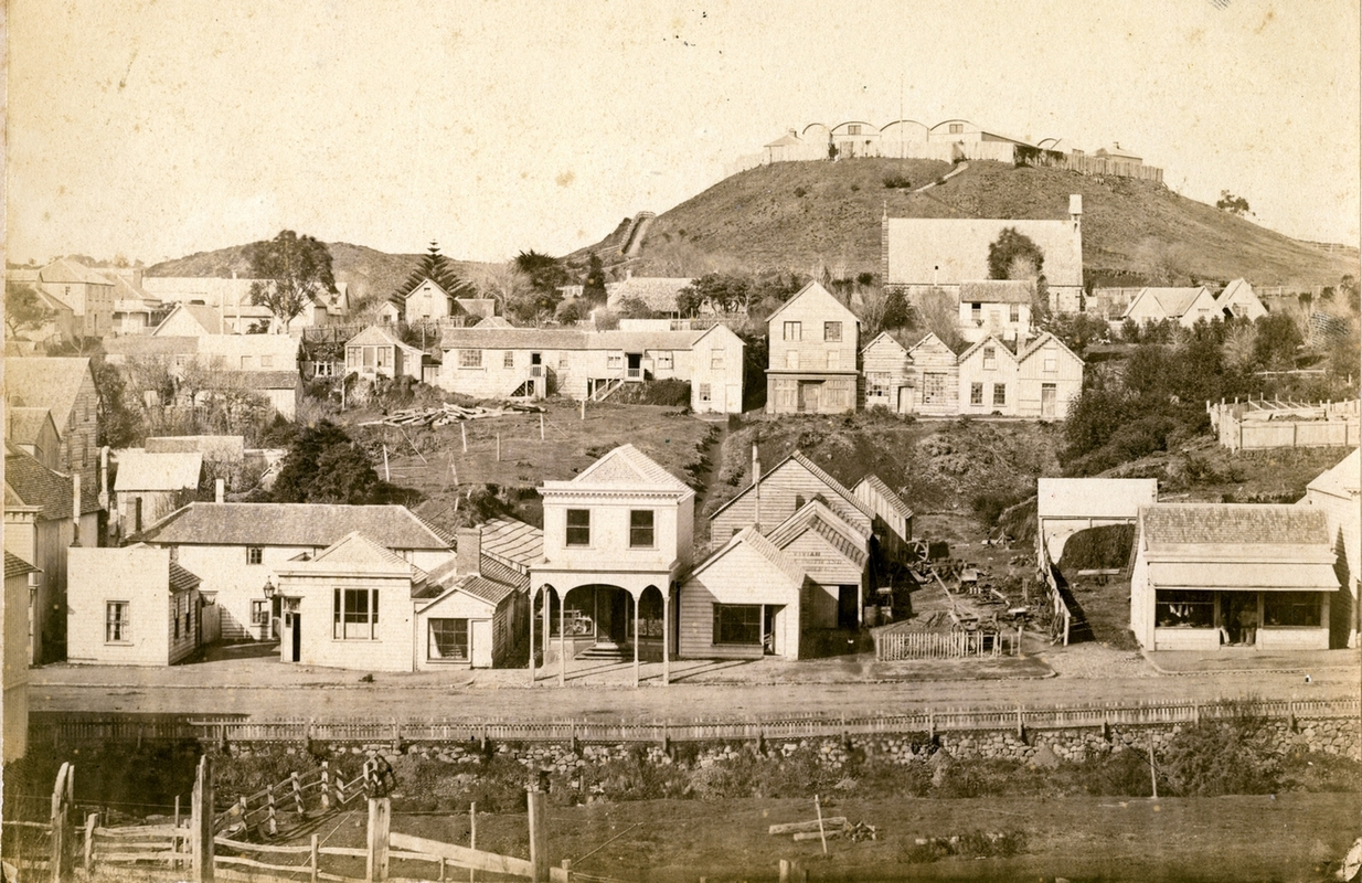 View of  the barracks on the Marsland Hill, showing the tightly-packed barrel-rooved buildings behind a wooden fance, above the  buildings among untidy piles of timber in the new town. Some buildings neat, but others ramshackle, and with a large, side-on  view of the massive church.