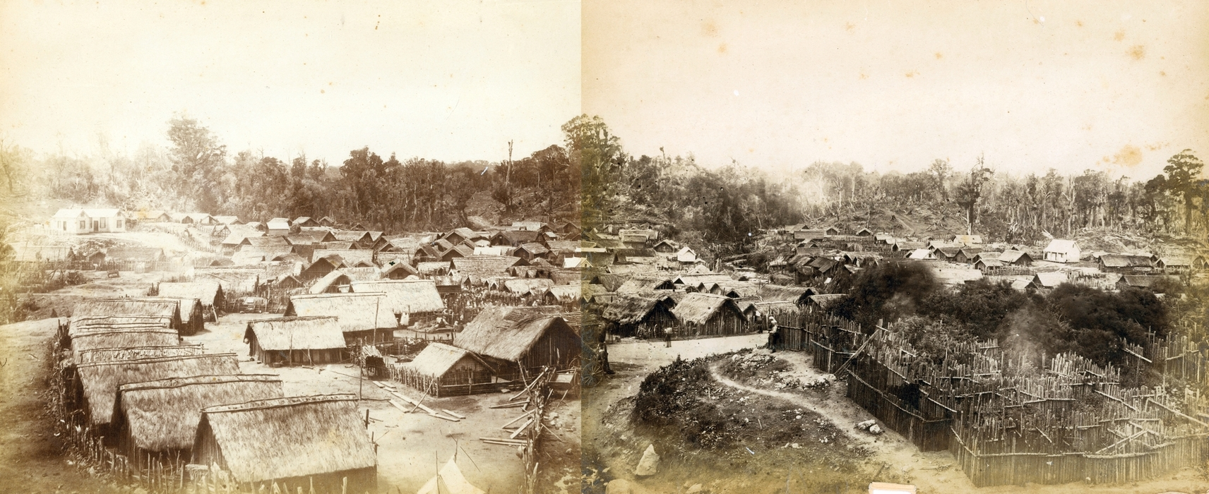 The joining isn't  perfect, but the two photographs were taken at the same time. A homestead on the left, on a raised mound, and about 80  thatched huts, trees in the background and a fenced area in the right foreground, possbily for animals and gardens.
