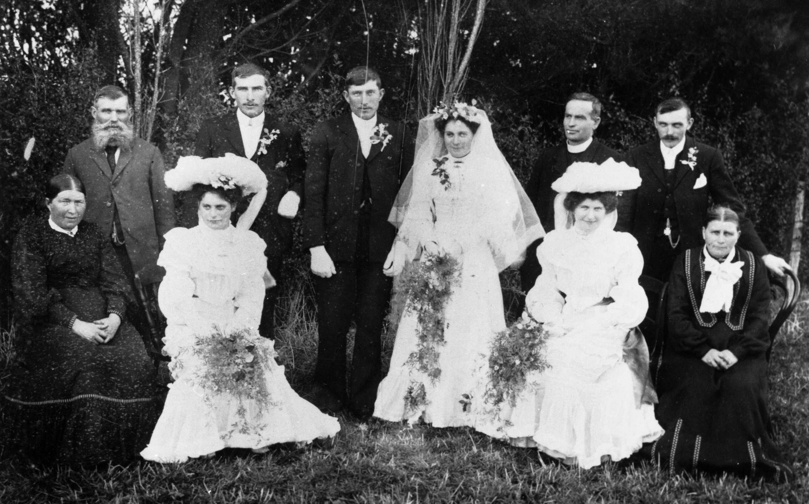 Black &  white photograph of the main wedding party taken in a garden.