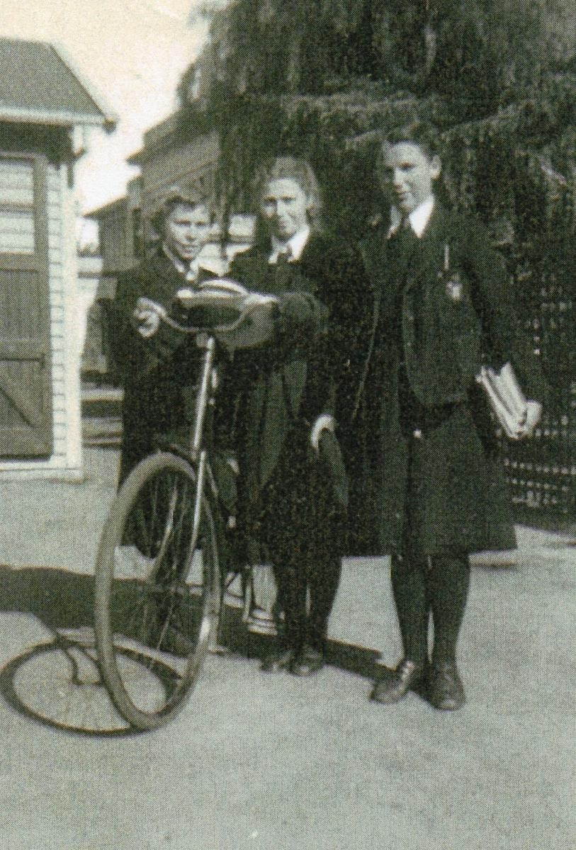 Three girls dressed in  dark school uniform, with blazers, the sisters holding huge bike.