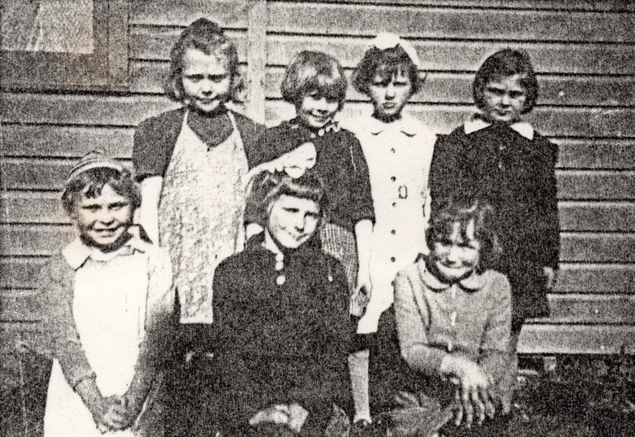 A grainy photograph of   Alina and six others, taken outside.