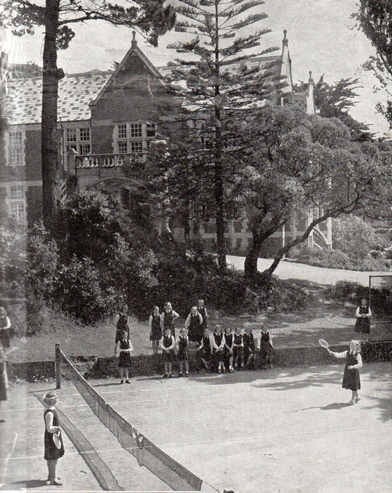 A wide shot of a tennis  court in the foregrund with main hostel behind trees making up most of the image. The girls are tiny.