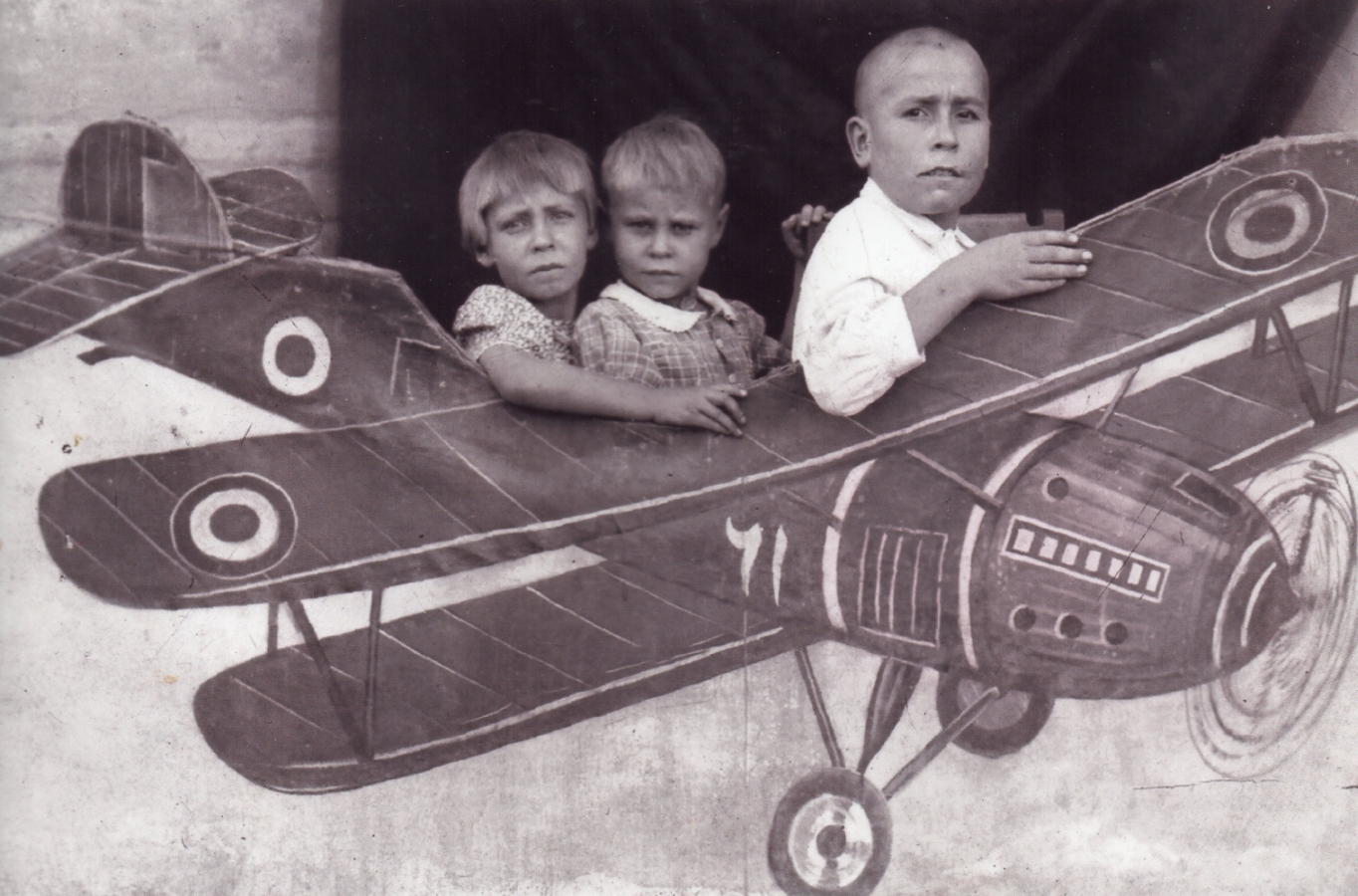 Danuta, Alina and  Tadeusz as the pilot in front, all looking very serious, sitting within a cut-out aeroplane.