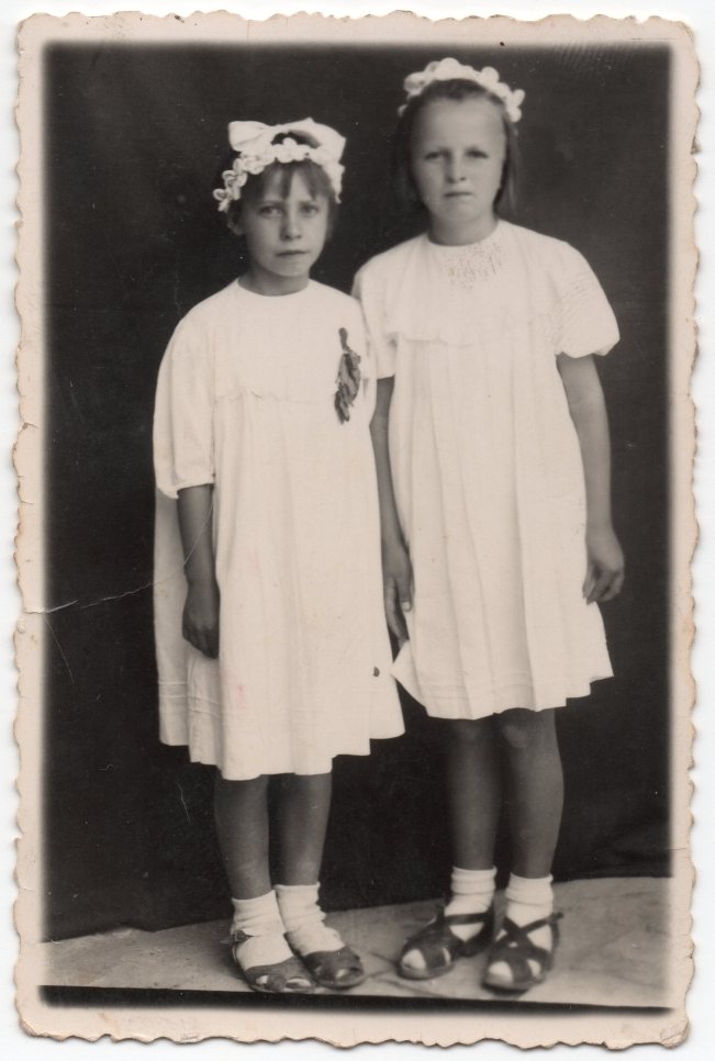 Danuta and a  friend pose in their white dresses. Plain dark background.