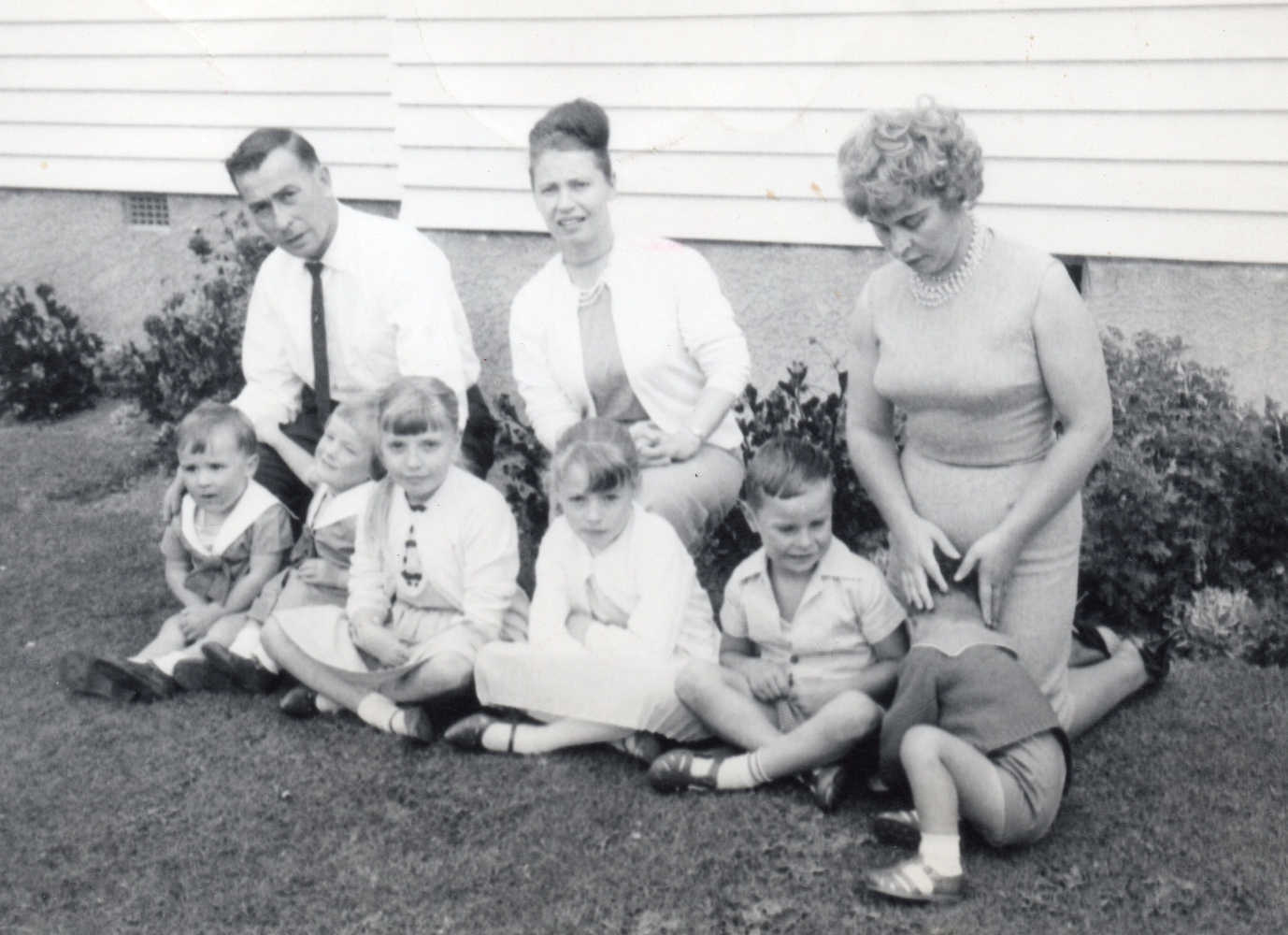 Zioło siblings,  each with two children, sitting on the grass in front of a house.