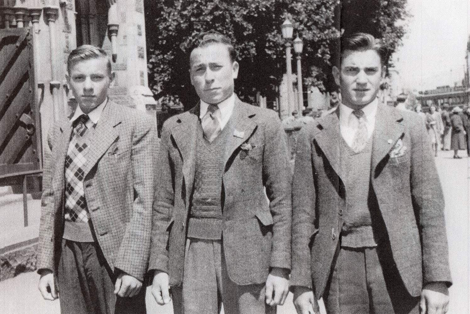 Three smartly-dressed young  men outside what looks like a church.