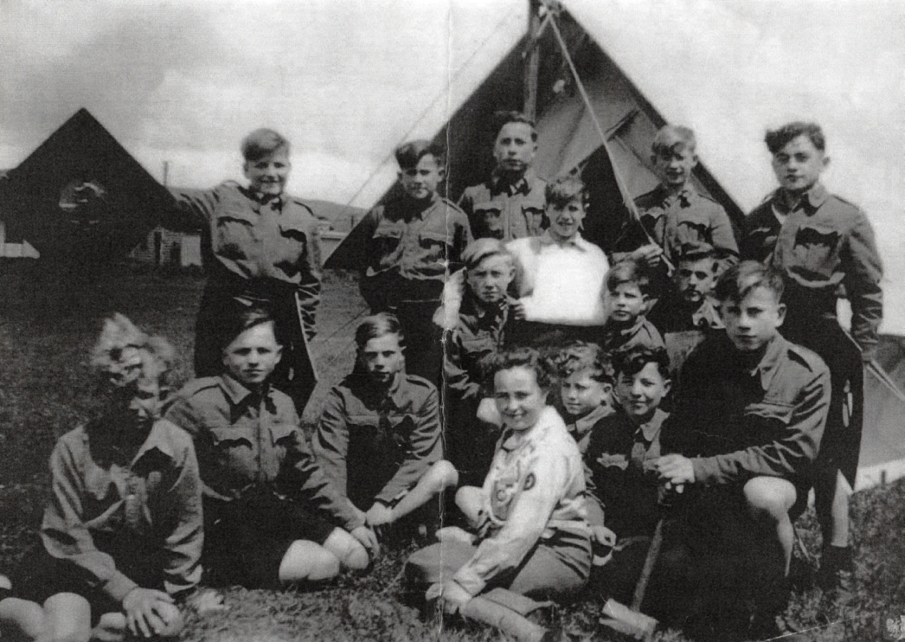 A group of boy scouts  in front of a tent and with their scout mistress sitting in front.