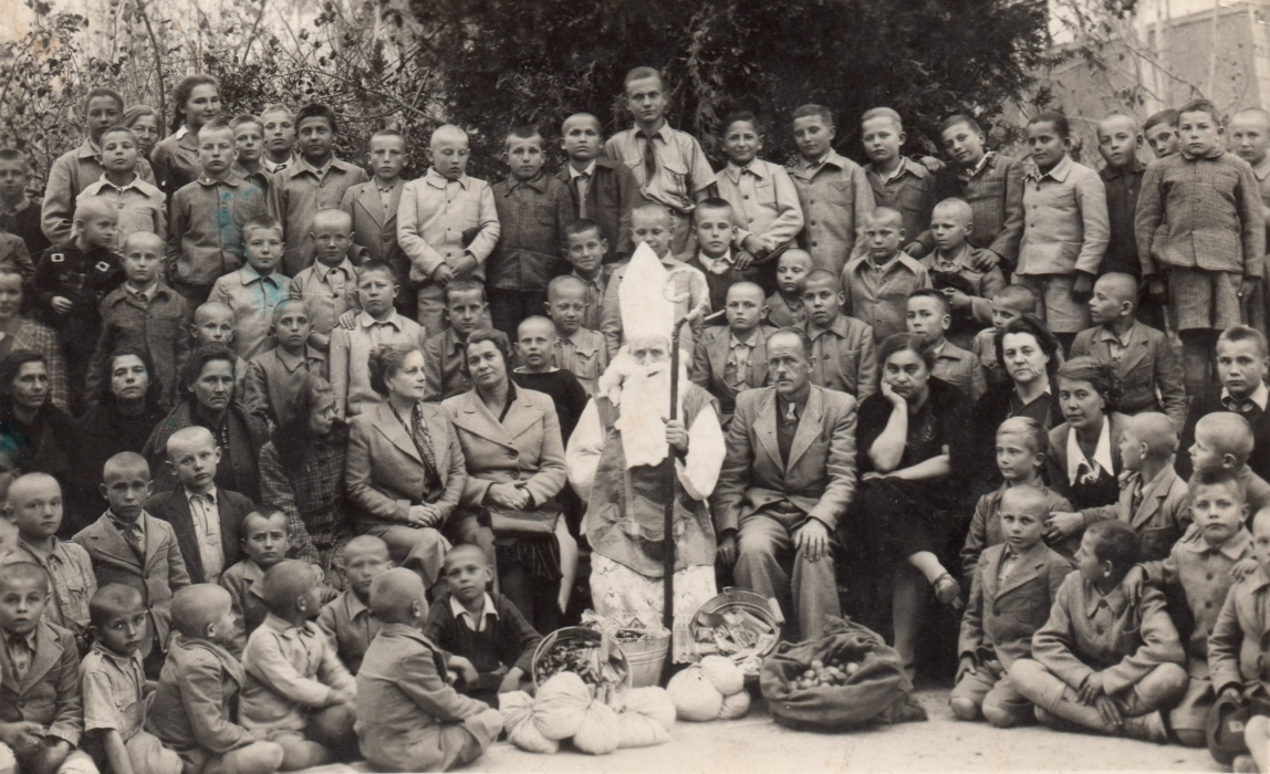 A large group of  mostly serious Polish children, with at least nine adults, surround St Nicholas.