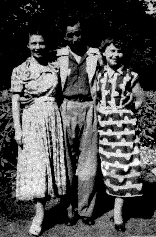 Black and white  photograph of Danuta, Tadeusz and Alina, taken outside in a garden.
