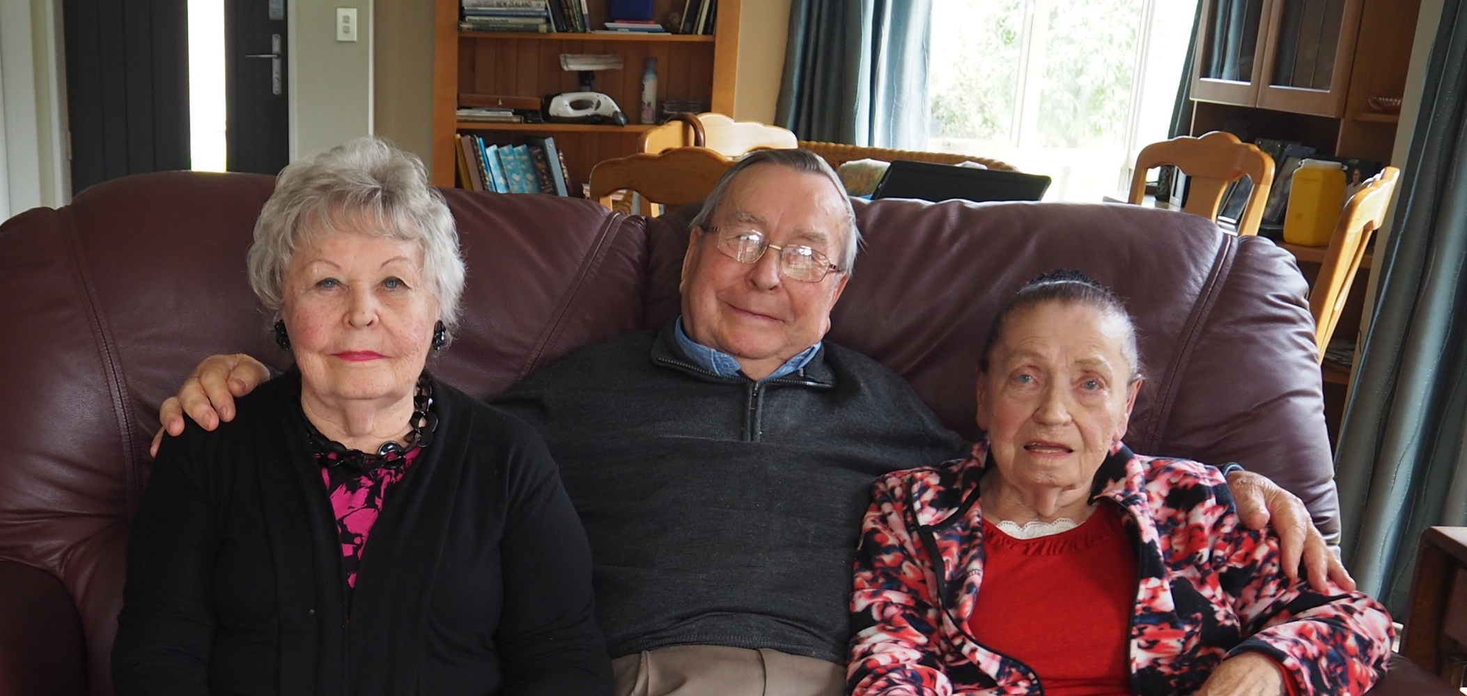 Tadeusz seated between his  sisters, on a couch in his lounge.