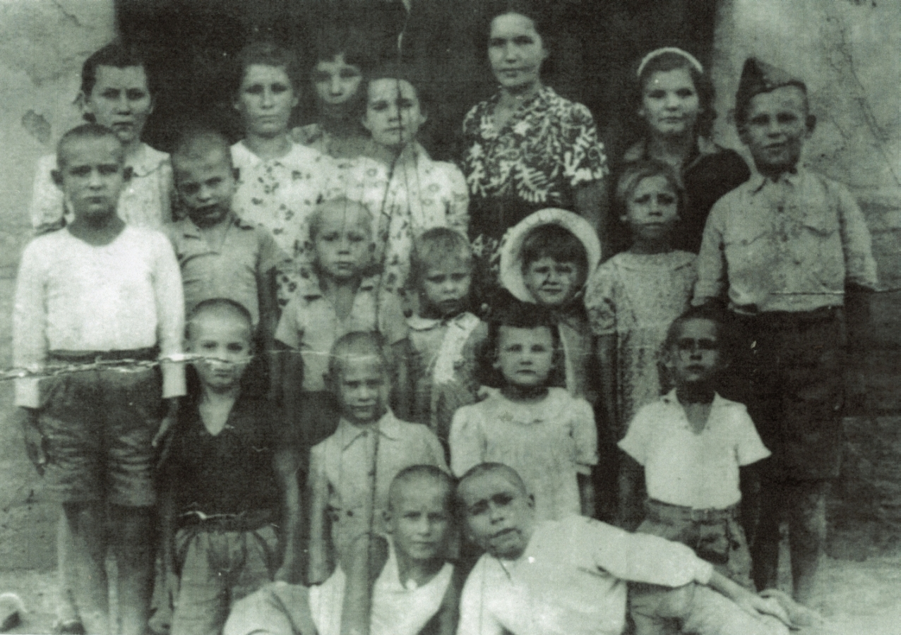 A group of Polish  children, with a woman. Alina, Danuta and Tadeusz are wearing the same clothes as the previous photograph.